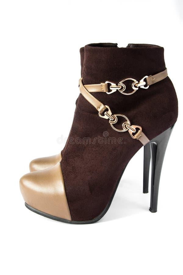 Fasionable brunissent des bottes de femmes de suède sur des talons hauts d'isolement sur le fond blanc images stock