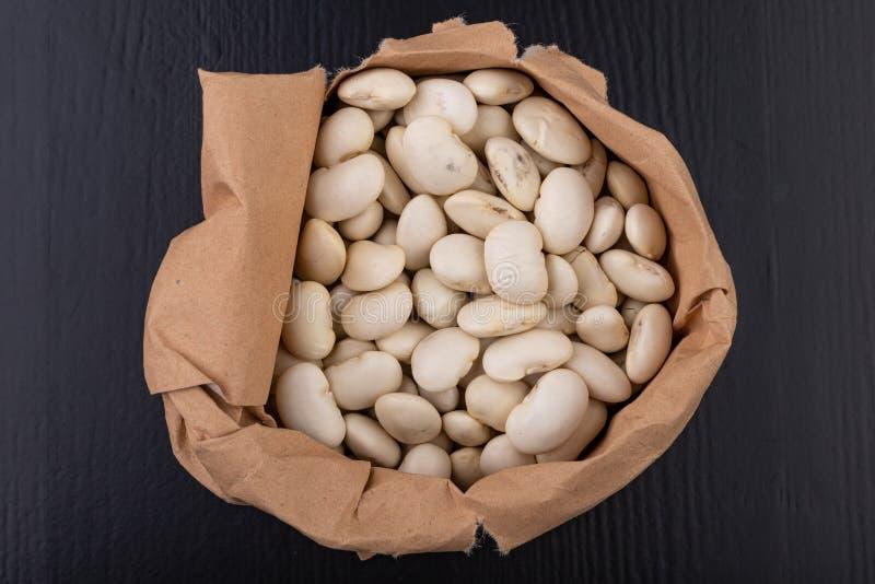 Fasola w papierowych torbach na kuchennym stole Karmowi składniki używać w kuchni fotografia royalty free