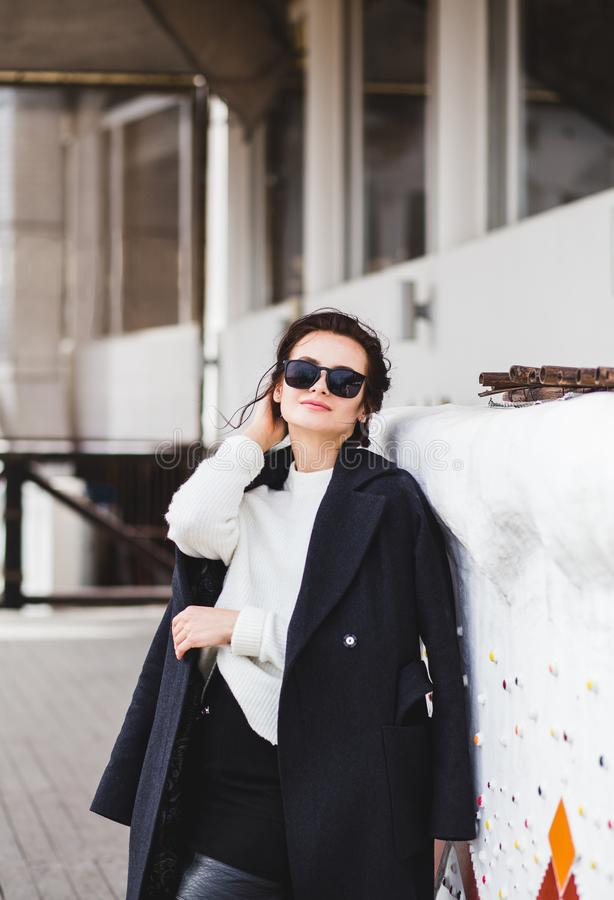 Fasonuje ładnego kobieta modela jest ubranym ciemnego żakiet białego pulower w okularach przeciwsłonecznych i, pozuje nad białym  zdjęcia stock