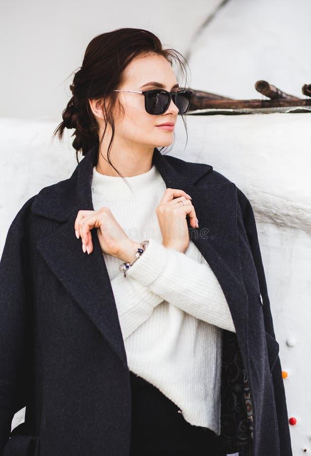 Fasonuje ładnego kobieta modela jest ubranym ciemnego żakiet białego pulower w okularach przeciwsłonecznych i, pozuje nad białym  zdjęcie stock