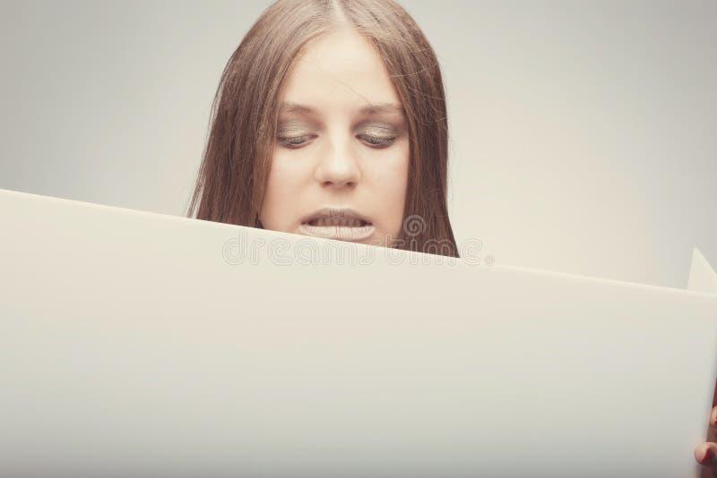 Fasonuje ładnej dziewczyny trzyma białą deskę z miejscem dla teksta Zdziwiona dziewczyna patrzeje wprawiać w zakłopotanie fotografia stock