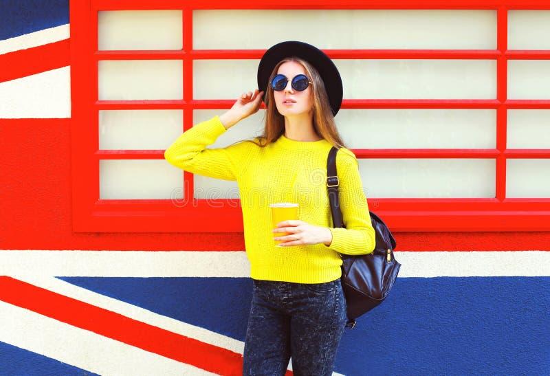 Fasonuje ładnej kobiety trzyma filiżankę nad kolorowy miastowym obrazy stock