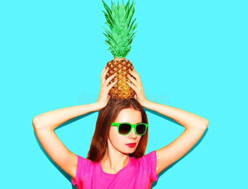 Fasonuje ładnej kobiety w okularach przeciwsłonecznych z ananasem nad błękitem obraz stock
