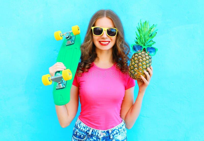 Fasonuje ładnej kobiety z deskorolka i ananasowymi okularami przeciwsłonecznymi ma zabawę nad kolorowym błękitem obrazy stock