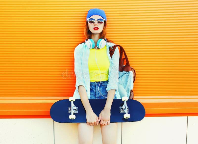 Fasonuje ładnej kobiety z deskorolka nad kolorową pomarańcze fotografia stock
