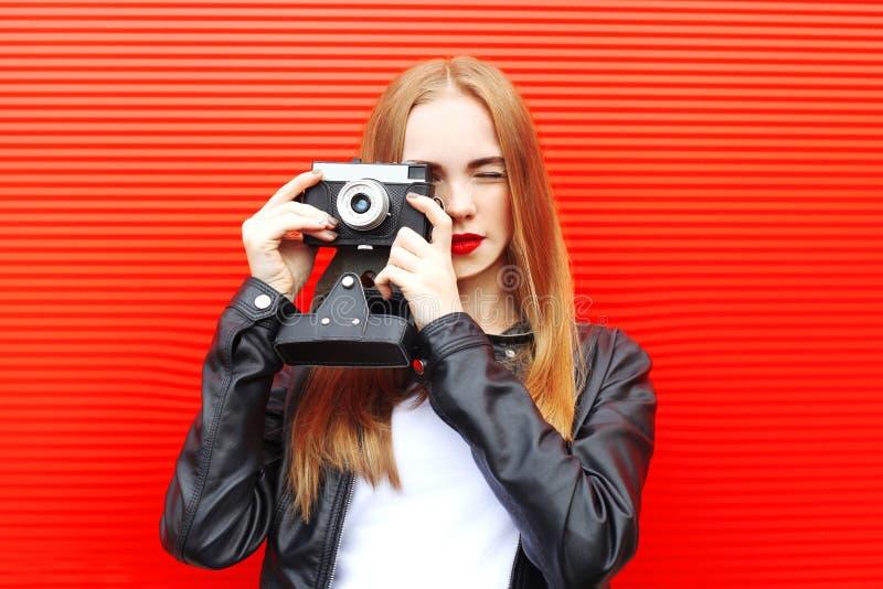 Fasonuje ładnej kobiety z rocznik kamerą w mieście nad czerwienią obrazy royalty free