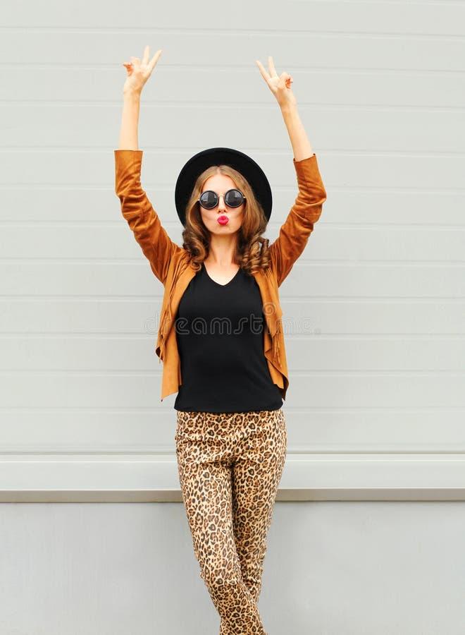 Fasonuje ładnej młodej kobiety jest ubranym czarnego kapelusz, okulary przeciwsłoneczni i kurtka podnosi ręki up nad miastowym tł zdjęcie stock