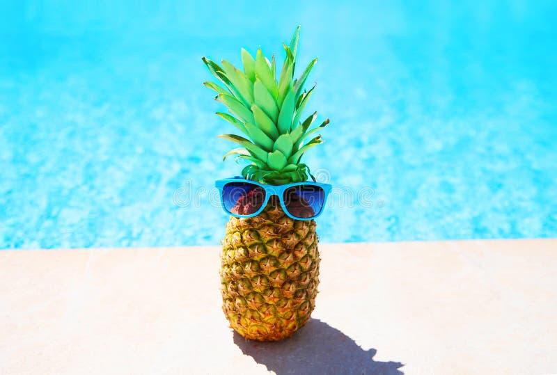 Fasonuje ananasa z okularami przeciwsłonecznymi na błękitne wody basenie obraz stock