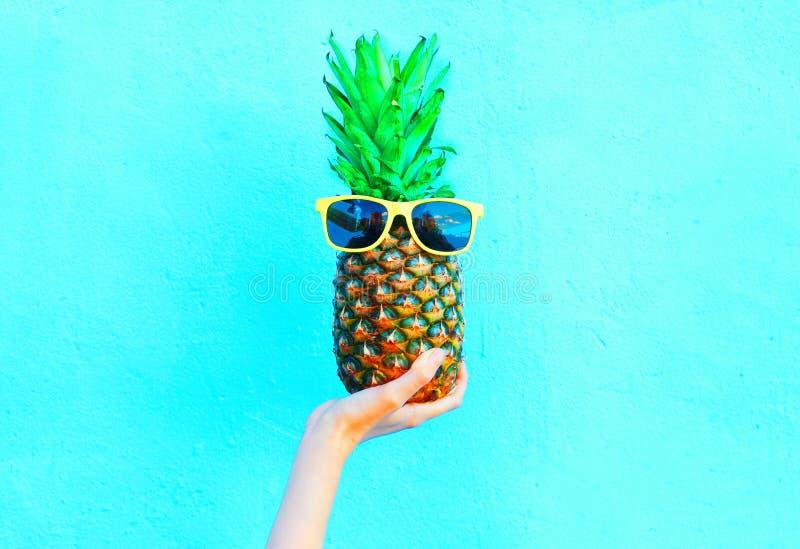 Fasonuje ananasa z okularami przeciwsłonecznymi na błękitnym tle, ręki ananas fotografia stock