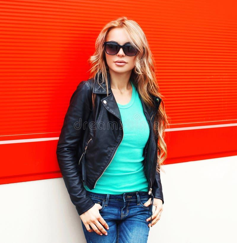 Fasonuje blondynki kobiety w okulary przeciwsłoneczni czerni skały kurtce przy miastem nad czerwienią obraz royalty free