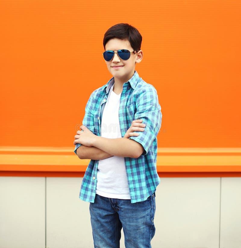 Fasonuje dziecko chłopiec być ubranym okulary przeciwsłoneczni i koszula w mieście obraz stock