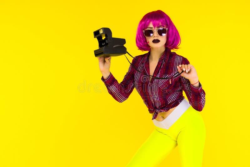 Fasonuje dziewczyna portret z kamerą na żółtym tle Szalona stylowa młoda kobieta w różowej peruce zdjęcia royalty free