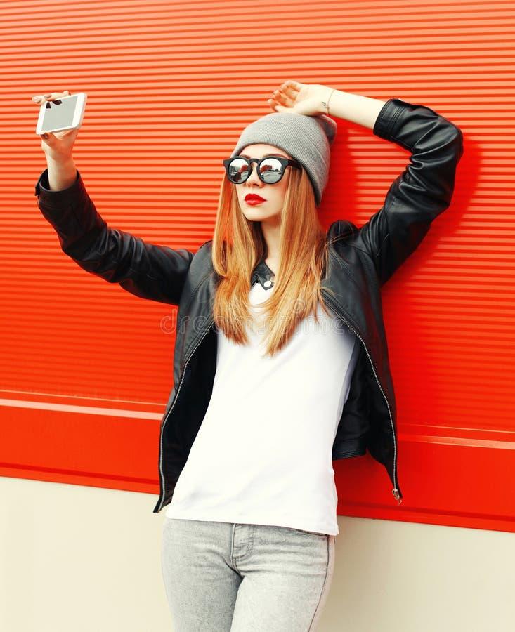 Fasonuje dziewczyny bierze autoportret na smartphone w mieście nad czerwienią obraz royalty free