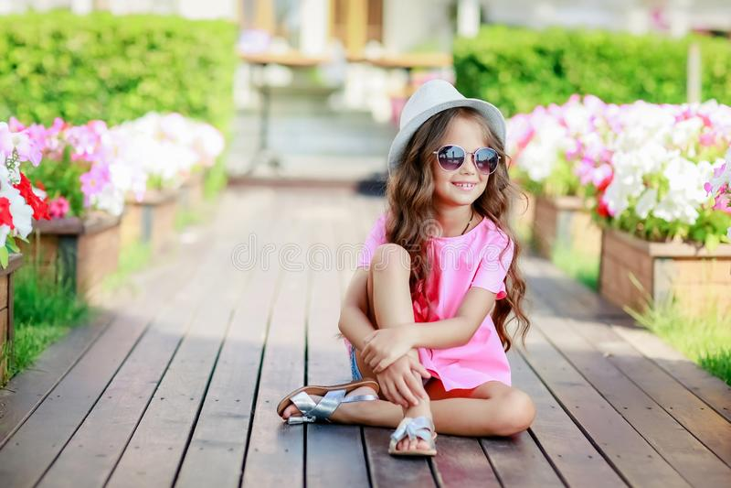 Fasonuje dziewczyny jest ubranym koszula, kapelusz i okulary przeciwsłonecznych w mieście różowych w kratkę, obrazy royalty free