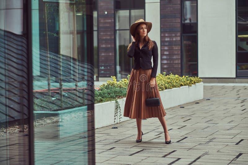 Fasonuje eleganckiej kobiety jest ubranym czarną kurtkę, brown kapelusz i spódnicę z torebki sprzęgła odprowadzeniem na Europejsk obrazy stock