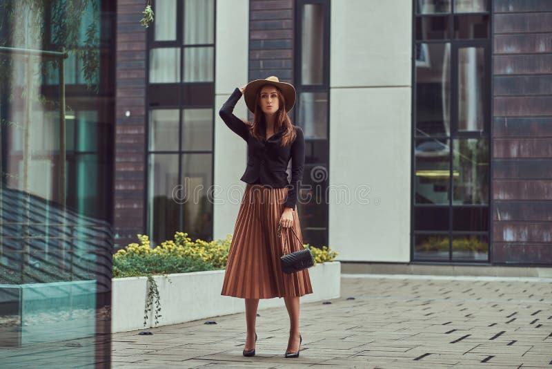 Fasonuje eleganckiej kobiety jest ubranym czarną kurtkę, brown kapelusz i spódnicę z torebki sprzęgła odprowadzeniem na Europejsk obraz stock