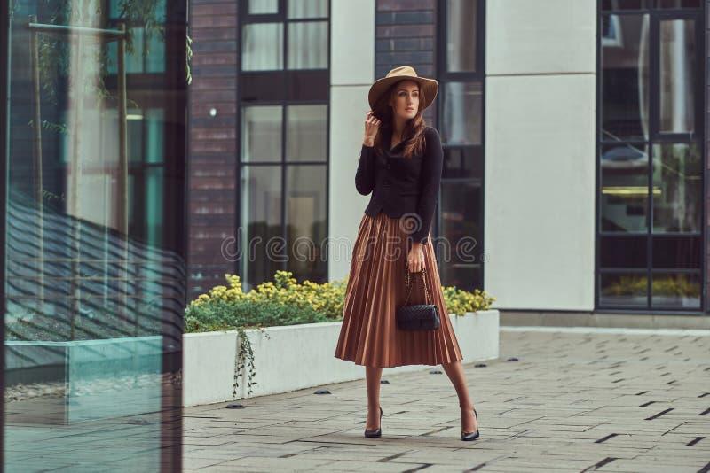 Fasonuje eleganckiej kobiety jest ubranym czarną kurtkę, brown kapelusz i spódnicę z torebki sprzęgła odprowadzeniem na Europejsk zdjęcia stock