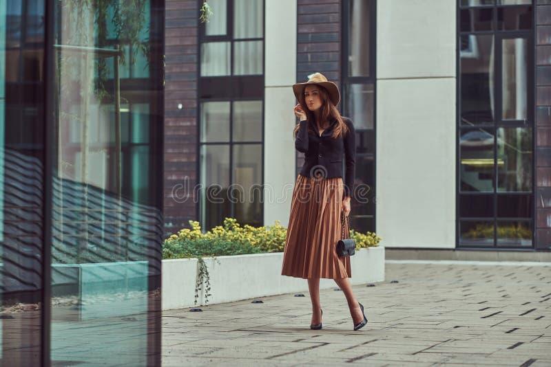 Fasonuje eleganckiej kobiety jest ubranym czarną kurtkę, brown kapelusz i spódnicę z torebki sprzęgła odprowadzeniem na Europejsk zdjęcie royalty free