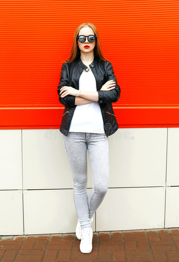 Fasonuje eleganckiej kobiety jest ubranym rockową czarną kurtkę i okulary przeciwsłonecznych w mieście nad czerwienią zdjęcie stock