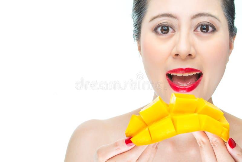 Fasonuje kobiety łasowania mango, zdrowie, piękno, makeup, kąsek, szczęśliwy zdjęcia stock