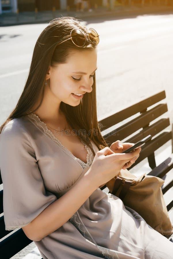 Fasonuje kobiety obsiadanie na ławce i używa mądrze telefon, ono uśmiecha się, w fotografia royalty free