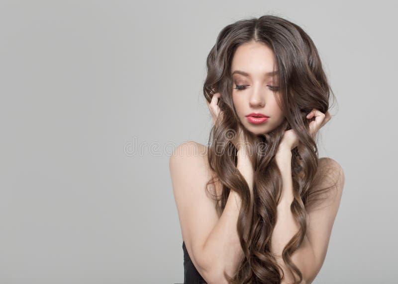 Fasonuje kobiety z pięknym długim i kędzierzawym włosy piękna kobieta makijaż zdjęcia stock