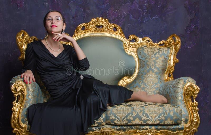 Fasonuje krótkopędu piękna azjatykcia kobieta w długim czerni sukni obsiadaniu na klasycznej kanapie krzesła wewnętrzny pobliski  zdjęcia royalty free
