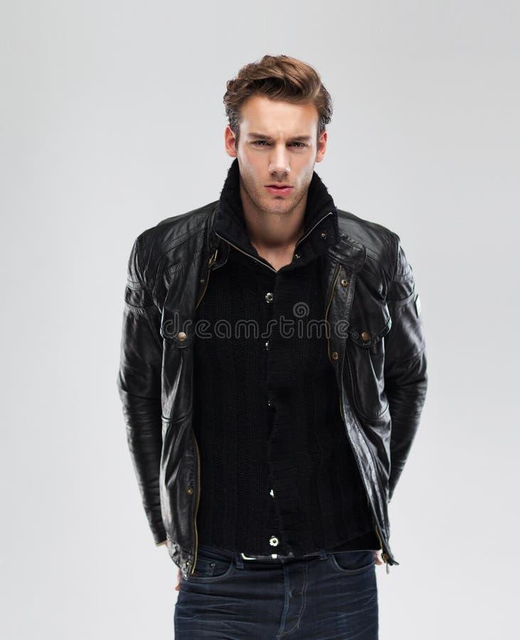 Fasonuje mężczyzna, wzorcowa skórzana kurtka, szary tło zdjęcie royalty free