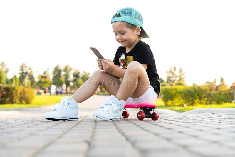 Fasonuje małej dziewczynki bawić się z smartphone obsiadaniem na deskorolka w parku zdjęcia stock