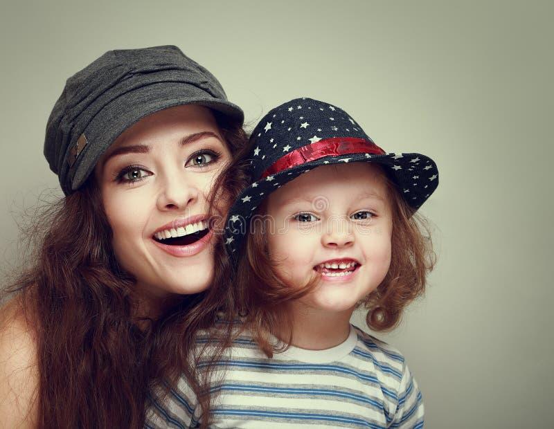 Fasonuje matki i dzieciaka z szczęśliwy uśmiecha się patrzeć w nakrętkach zdjęcie stock