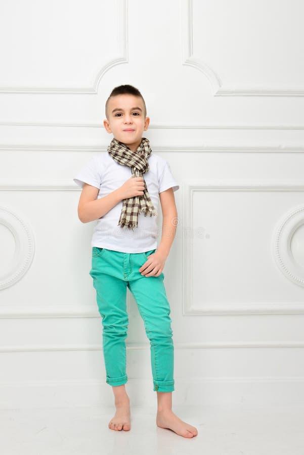 Fasonuje pięknej chłopiec w jaskrawy szalik, spodniach i koszulka i fotografia stock
