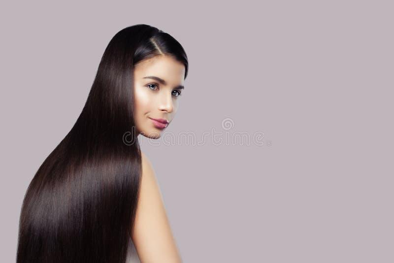 Fasonuje piękno portret śliczna brunetki kobieta z długim zdrowym włosy na różowym tle obrazy royalty free