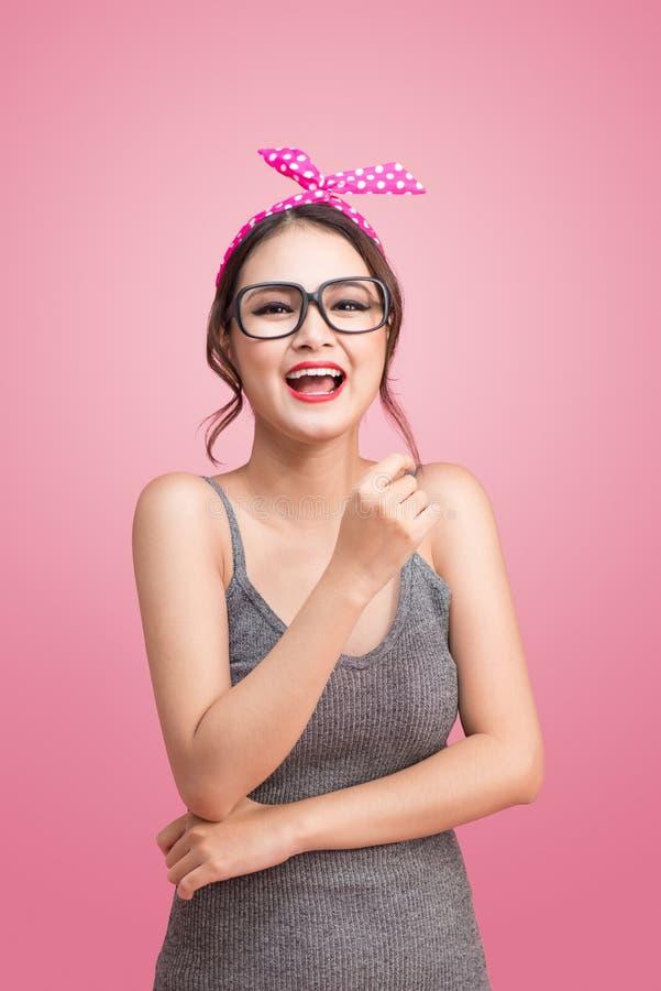 Fasonuje portret azjatykcia dziewczyna stoi na menchiach z okularami przeciwsłonecznymi obrazy stock