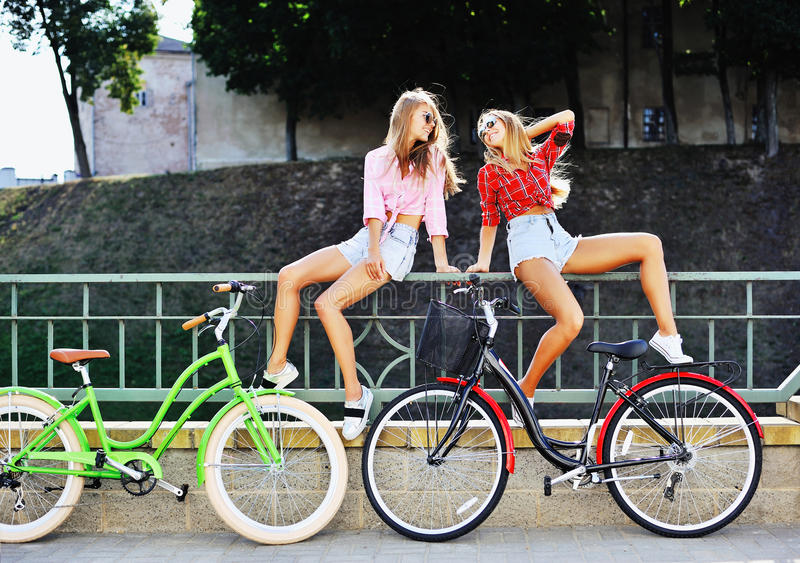 Fasonuje portret dwa seksowna kobieta na bicykle w lecie obraz stock