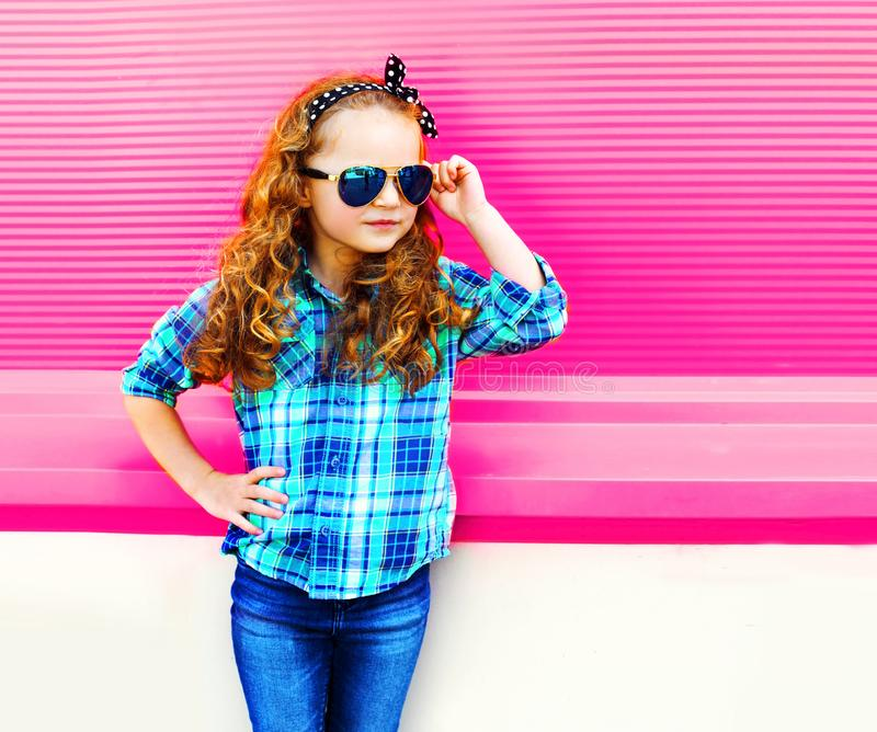 Fasonuje portret małej dziewczynki dziecka w w kratkę koszula, okulary przeciwsłoneczni pozuje na kolorowych menchiach zdjęcia stock