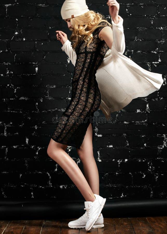 Fasonuje portret modna dziewczyna z blondynem, będący ubranym czarnej sukni i kurtki pozycję przeciw czarnej miastowej ścianie zdjęcie royalty free