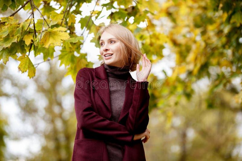 Fasonuje portret piękna blondynka kobieta w eleganckim odziewa w jesień parku zdjęcia royalty free
