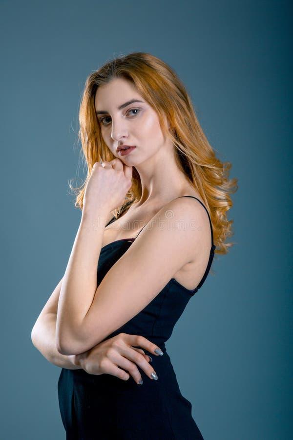 Fasonuje portret piękna młoda kobieta z czerwonym włosy Dziewczyna w czerni sukni na błękitnym popielatym tle zdjęcia royalty free