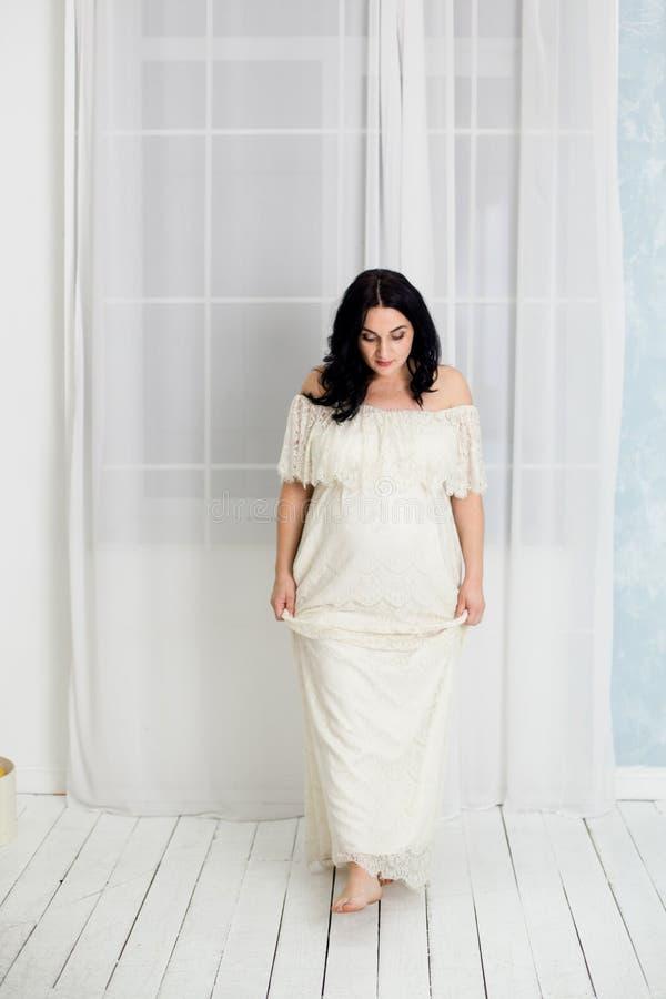 Fasonuje portret szczęśliwa kobieta w ciąży w biel sukni obraz royalty free