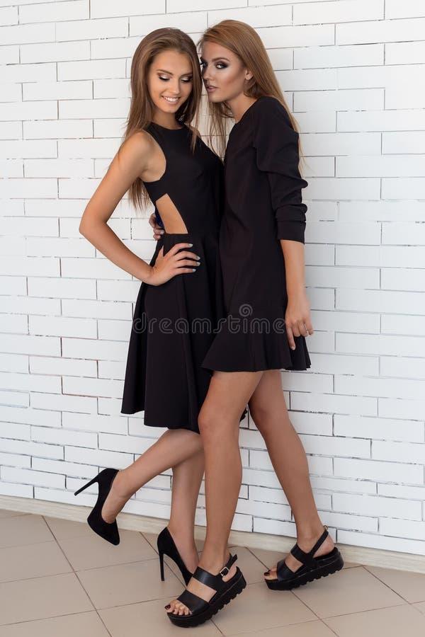 Fasonuje strzał dwa pięknej dziewczyny w seksownej czerni sukni przeciw tłu ceglana biel ściana w studiu obraz stock