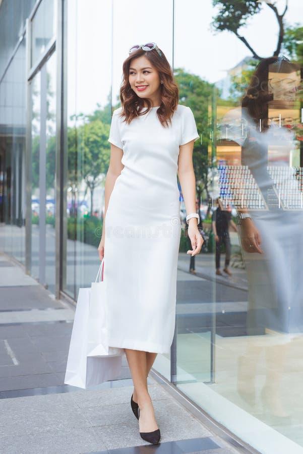 Fasonuje styl życia portreta młodej azjatykciej dziewczyny z torbami na zakupy chodzącymi za sklepie od, zdjęcia royalty free
