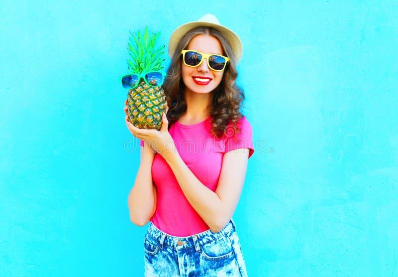 Fasonuje uśmiechniętej kobiety jest ubranym lato kapelusz ma zabawę nad kolorowym błękitem z ananasowymi okularami przeciwsłonecz fotografia stock