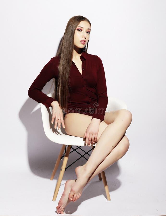 Fasonuje ubierającej młodej kobiety z długie włosy obsiadaniem na krześle Nad bia?ym t?em Luksusu styl zdjęcie royalty free