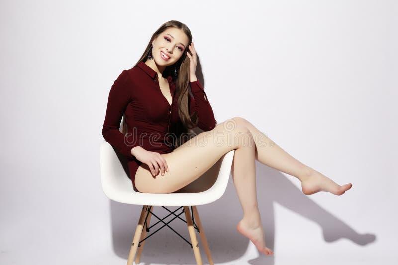 Fasonuje ubierającej młodej kobiety z długie włosy obsiadaniem na krześle Nad bia?ym t?em Luksusu styl fotografia stock