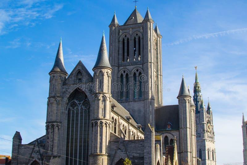 Fassade der Kirche St. Nikolaus-Niklaaskerk mit dem Uhrturm von Belfry von Gent Het Belfort im Hintergrund, in stockbilder