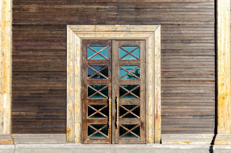 Fassade des Errichtens - hölzerne Wand, eine Tür mit Glaseinsätzen stockbild