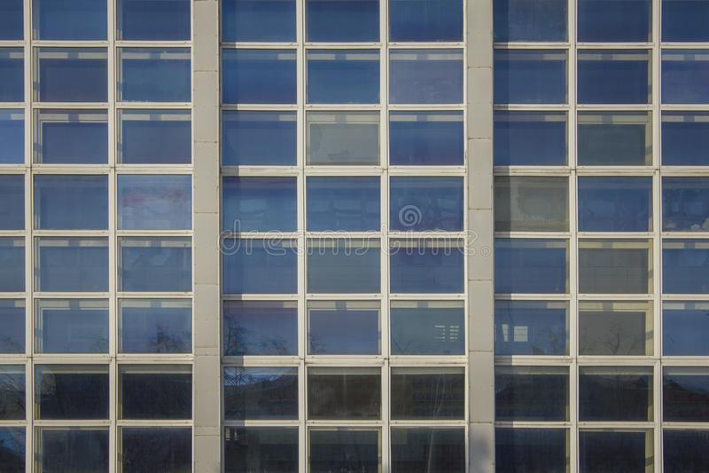 Fassade des hohen modernen Glasgebäudes mit quadratischen Fenstern und eine Reflexion des blauen Himmels stockfotografie