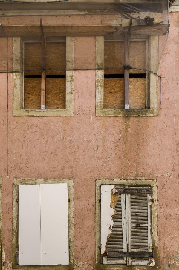 Fassade des verlassenen, verfallenen Hauses mit 4 verschalte Fenster, Fensterläden, Bretter und Fluss als Schutz vor fallenden Fl stockfotografie