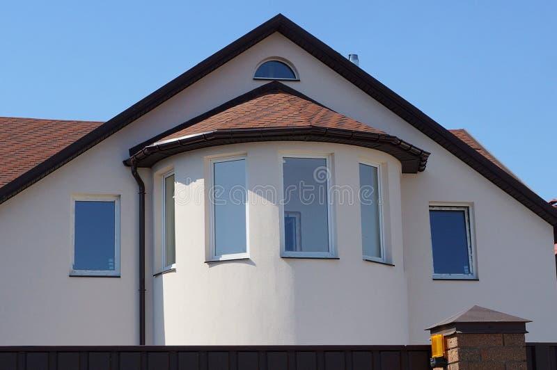 Fassade eines großen Hauses mit einem Dachboden und Fenster und braune Fliesen auf dem Dach gegen den Himmel stockfotos