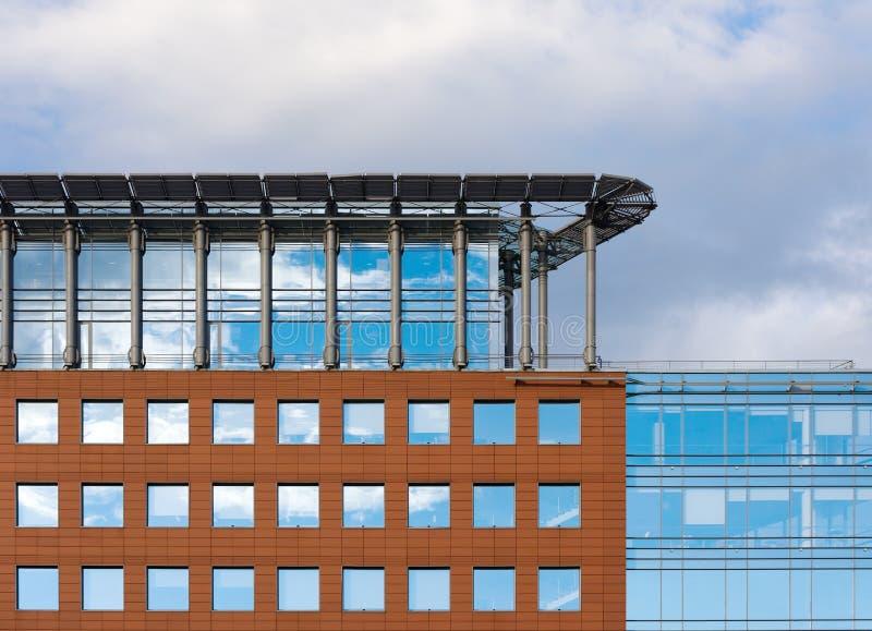 Fassade eines modernen Bürohauses Quadratische Fenster, Dachbodenboden und bewölkter Himmel stockfotos